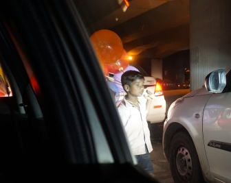 A young boy sells balloons on the highway in Delhi.